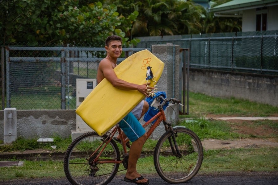 Tahitian surfer on bicycle in Moorea